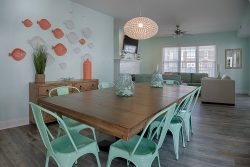 beach themed dining area with teal chairs and coral accents