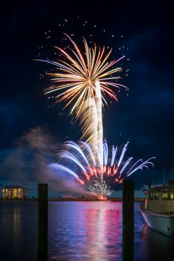 fireworks explode over the bay in Crisfield Maryland as onlookers on a boat watch