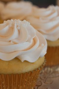 yellow cupcakes with cream icing and white sprinkles
