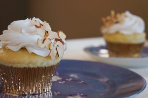 yellow cupcakes with white frosting and almond garnish on blue plates