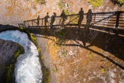 gorge with water rushing through and the shadows of people standing on a bridge above it