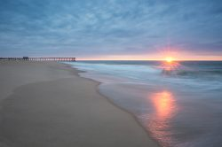 waves coming in at Ocean City as the sun peaks above the horizon with the pier in the background