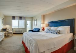 red and blue nautical oceanfront hotel room with bed sofa and dining area