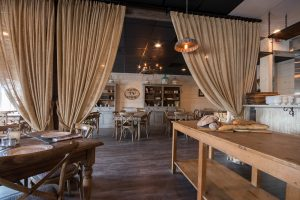 rustic restaurant with wooden tables and burlap curtains
