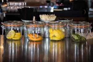 orange lemons and lime in mason jars used for garnishing drinks at a bar
