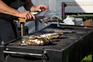 catering chef lifts fish off a grill at an outdoor catering event