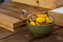charred lemons in a bowl with tongs on a wooden butcher block