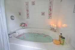 bed and breakfast bath with candles and rose petals