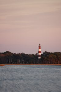 lighthouse on chincoteague island at sunset as the water is blown