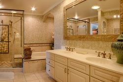 Master bathroom with gold accents two sinks large bathtub and walk in shower