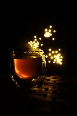 steaming cup of tea against a dark background