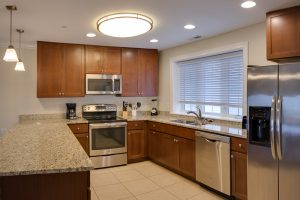 modern kitchen with dark cabinetry and stainless steel appliances