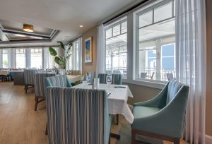 fancy oceanfront restaurant with upholstered chairs and wine glasses on table