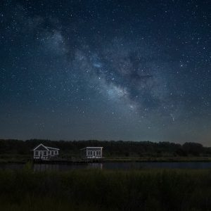 two boat houses at night with milkyway background