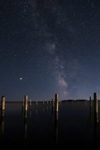 pilings in the water at night with milkyway galaxy
