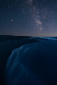 ocean beach at night with milky way galaxy