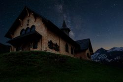 church on hill at night with stars snowy mountains in background