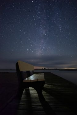 bench on dock at night with stars milkyway