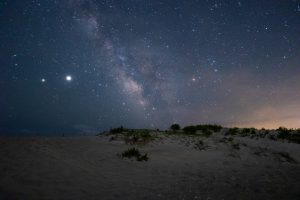 milky way stars across the sky above sand dunes on the beach